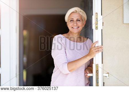 Smiling woman standing in doorway of her house