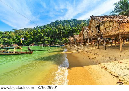 Traditional Long-tail Boats And Houses Of Moken Tribe Village Or Sea Gypsies And Tropical Waters Of