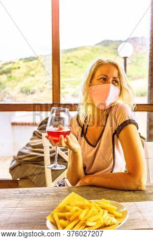 Tourist Woman Having An Aperitif With Surgical Mask. Drinking A Red Wine Glass With Fries In An Ital