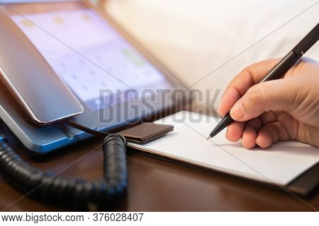 Businessman Manager Signing Document Report Note On Paperwork At Desk Phone Beside The Bed In Hotel,