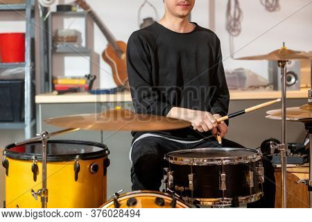 Young musician in casualwear beating one of drums with wooden drumsticks while sitting by drum kit during rehearsal in garage
