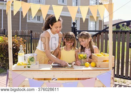 Young brunette woman drawing glass of drink on noticeboard with chalk while her daughters standing near by and selling lemonade by stall