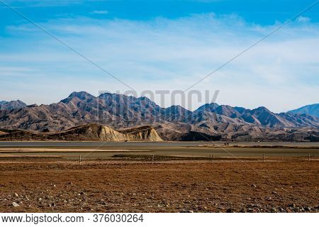 The Extreme Arid Dry Terrain Around Lake Grassmere With A  Dramatic Rugged Mountain As A Backdrop