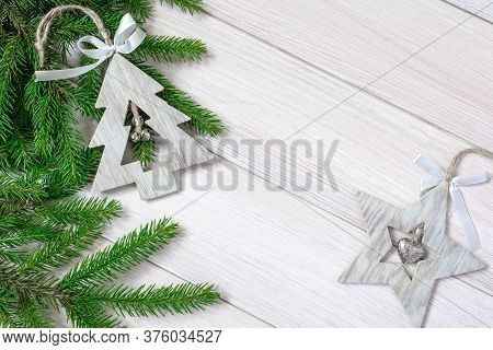 Christmas Or New Year Decorations Background: Tree Branches And Wooden Christmas Toys In The Form Of