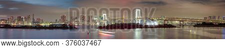 Tokyo Destinations. View Of Renowned Rainbow Bridge In Odaiba Island In Tokyo At Twilight With Line