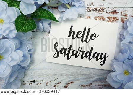 Hello Saturday Card With Blooming Flower On Wooden Background