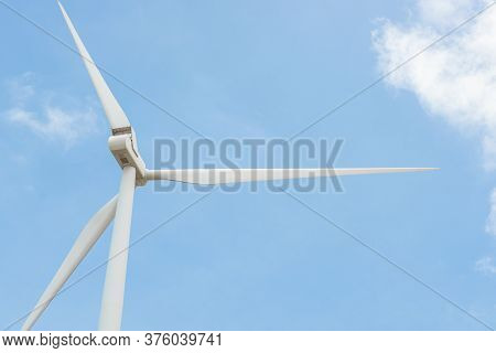 Close-up Wind Turbine In Rotation To Generate Electricity Energy On Outdoor With  Blue Sky Backgroun