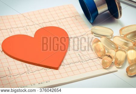 Medical Stethoscope, Tablets And Heart Shape On Electrocardiogram Graph. Medicine And Healthy Lifest