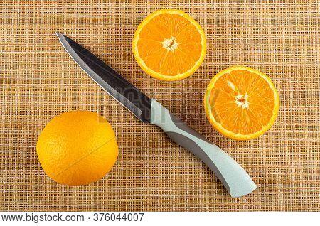 Full Fresh Orange, Kitchen Knife, Two Halves Of Orange On Brown Mat. Top View