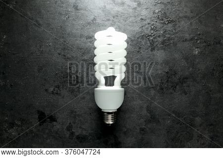 Single energy efficient light bulb glowing brightly in a dark room. New, modern, or unique energy saving idea concept.
