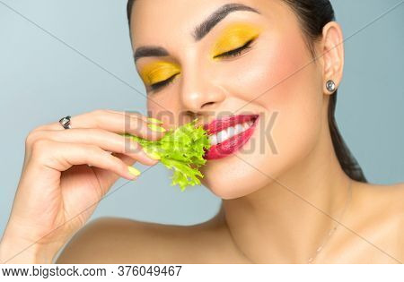Healthy eating, diet. Beautiful healthy girl eating raw vegan food and smiling. Beauty young fashion woman eats green fresh lettuce salad leaf, organic vegetables. Vegetarian concept. Makeup and nails