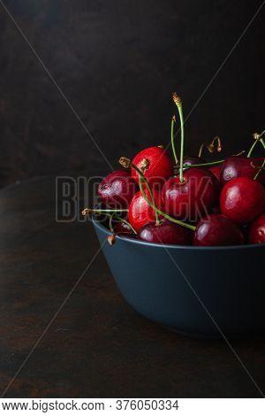 Cherry, Water Drops On Bawl On Dark Wooden Table. Ripe Ripe Cherries. Sweet Red Cherries. Top View.
