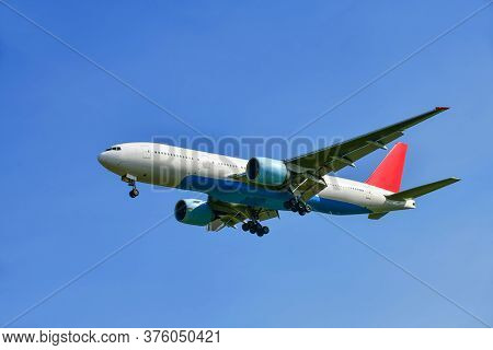 Commercial Airplane Isolated On A Blue Sky Background