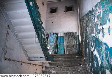Stairs Inside The Destroyed Building. Shabby Paint, Tattered Walls And Doors. Desolation And Despond