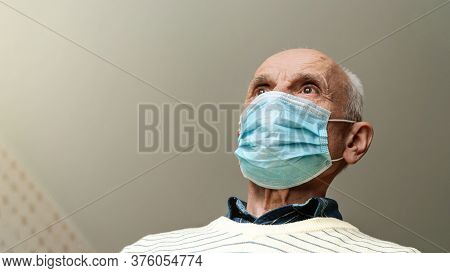 Bald Pensioner In Blue Mask And Yellow Pullover Stands Against Ceiling At Home Coronavirus Isolation