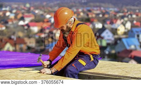 Roofer Worker In Special Protective Work Wear. New Roof Under Construction Residential Building. Bui