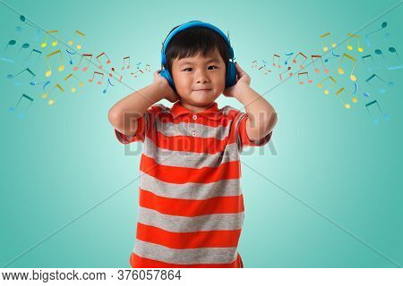 Music,childhood And Technology Concept.asian Little Boy With Headphone Over Green Background With Mu