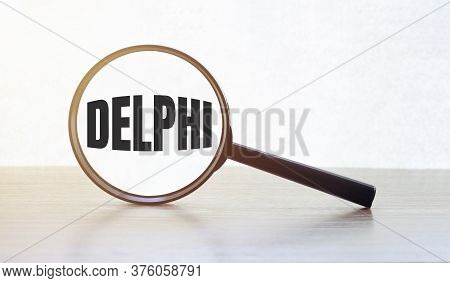 Magnifying Glass With Text Delphi On Wooden Table.