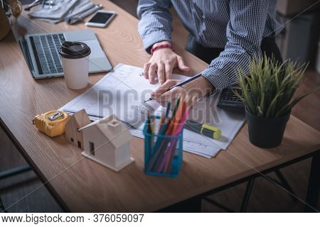 Architect Woman is Working Architecture Drawing Layout and Detail Drafting on Table Desk in Home Office, Female Designer is Creative Sketching for Construction. Architect Occupation/Creativity Concept