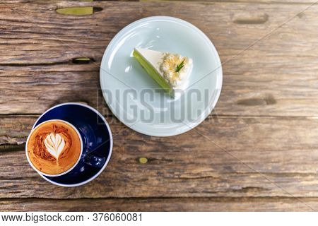 Top View Of Hot Cappuccino Coffee And  Home Made Cake In The Cafe, Heart Shaped Cappuccino Coffee In