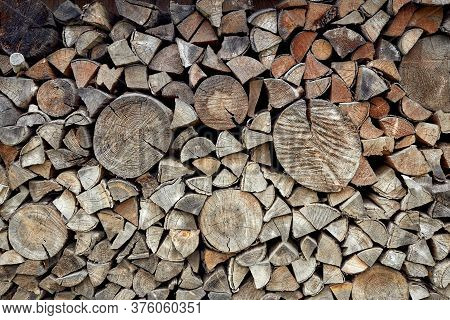 Wall Firewood. Background Of Old Dry Chopped Firewood Logs In Stacks.