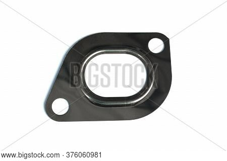 Metal Gasket Of The Exhaust Manifold Of The Car On An Isolated White Background. Spare Parts.