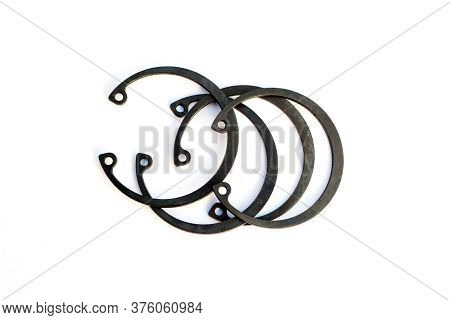 Black Circlip Retaining Rings Scattered On A White Background.