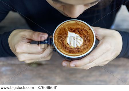 Top View Of Hot Cappuccino Coffee In The Cafe, Heart Shape Cream Coffee In Blue Cup. Hands Women Hol