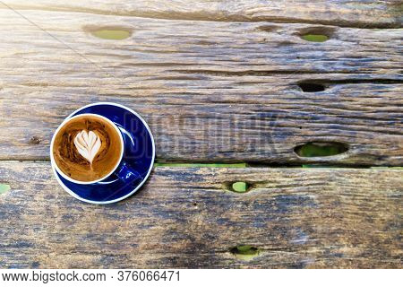 Top View Of Hot Cappuccino Coffee In The Cafe, Heart Shaped Cream Cappuccino Coffee In Blue Cup On A