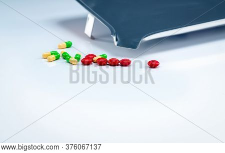 Red Tablets And Green-yellow Capsules Pills With Drug Tray On White Table. Pharmaceutical Industry.