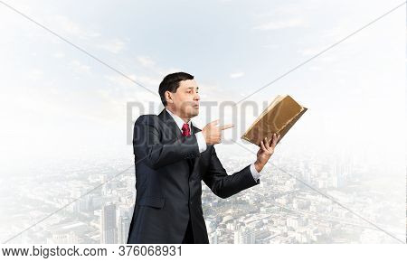 Senior Businessman Finger Pointing Into Open Old Book. Portrait Of Adult Man In Business Suit And Ti