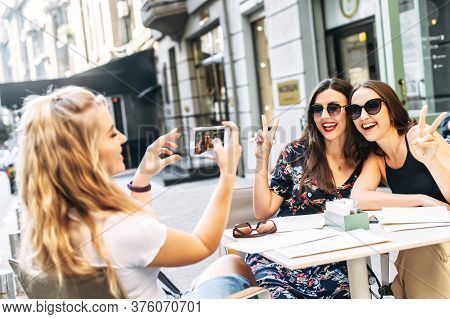 Female Friends Spend Time In The Summer Cafe. Two Attractive Young Girls Pose While Other Girl Takes