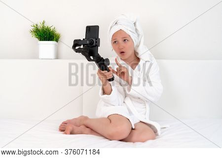 A Teenager Girl Blogger Sits On A Bed In A White Bathrobe With A Towel On Her Head, Face Patches On