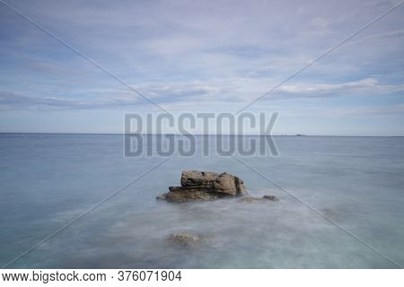 Magnificent Scenery Of Sea With Stone Against Blue Sky With Clouds During Daytime In Long Exposure
