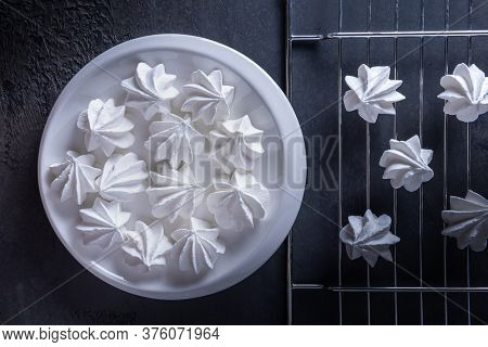 Still Life With Few White Meringue Cookies On White Porcelain Round Plate And On Metal Grate. Textur