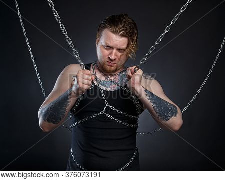 Photo Of A Tattooed Brutal Man Bound In Chains