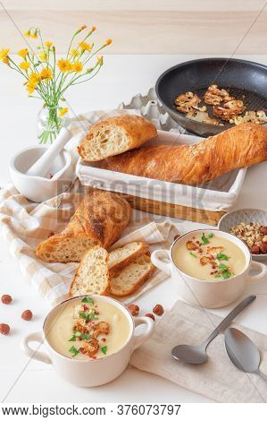 White Wooden Table With 2 Bowls Of Cauliflower Soup Embellished With Crushed Hazelnuts, Red Pepper,