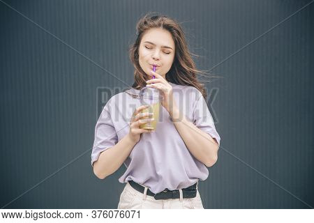 Young Stylish Trendy Woman Isolated Over Grey Blue Background. Dreamy Girl Drink Cocktail Or Lemonad