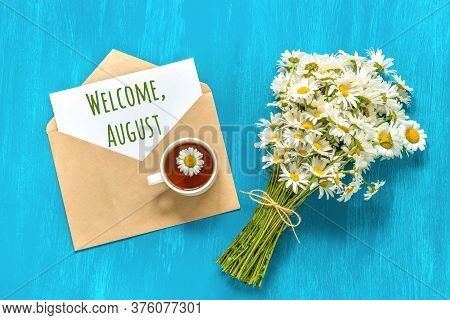 Welcome August Text On White Card In Craft Envelope, Bouquet White Chamomiles Flowers And Cup Of Tea