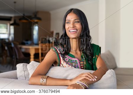 Cheerful indian woman in traditional clothing sitting on couch and laughing. Beautiful girl in sari with a bindi on forehead looking away and smiling. Happy hindu wife in saree relaxing at home.