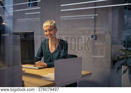 Smiling cool business woman working on desktop computer late at night. Beautiful stylish business woman working. Portrait of trendy girl using computer late in the evening in office with copy space.