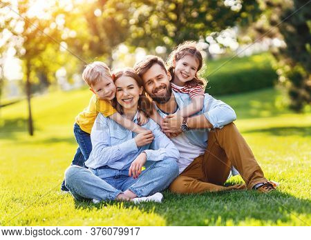 Cheerful Boy And Girl Embracing Happy Parents From Behind And Looking At Camera While Resting On Gre