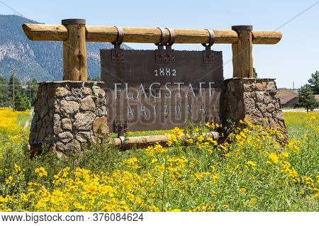 Entering Sign Of The City Flagstaff With Yellow Flowers. Flagstaff Is A City In The U.s. State Of Ar