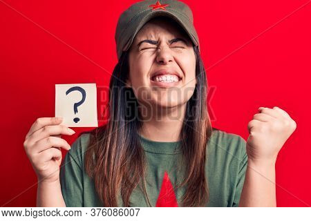 Beautiful woman wearing cap with red star communist symbol holding question mark reminder screaming proud, celebrating victory and success very excited with raised arm