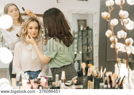 Make-up Artist Applying Eyeshadows While Hairdresser Making Hairstyle In Dressing Room In Front Of T