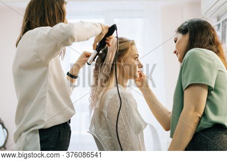 Preparation Process Of Gorgeous Young Woman, Hairdresser Is Twisting Long Fair Hair, Female Make-up
