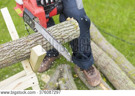 Electric Saw In Action Cutting Wood. Man Cutting Tree Trunk Into Logs With Saw In Motion. Close Up O