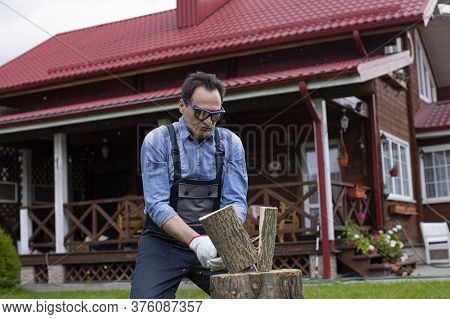 Strong Man Woodcutter In Working Uniform Chopping Wood With Sharp Ax On Wooden Hemp, Sawdust Fly To