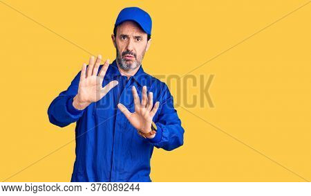 Middle age handsome man wearing mechanic uniform moving away hands palms showing refusal and denial with afraid and disgusting expression. stop and forbidden.