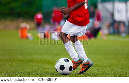African American Boy In Junior Football Team Leading Ball On Grass Training Field. Youth Soccer Play
